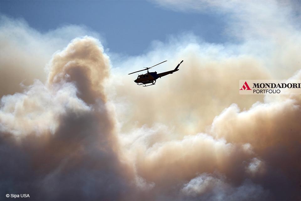 Un elicottero vola vicino al Woolsey Fire che brucia nella zona delle montagne di Santa Monica