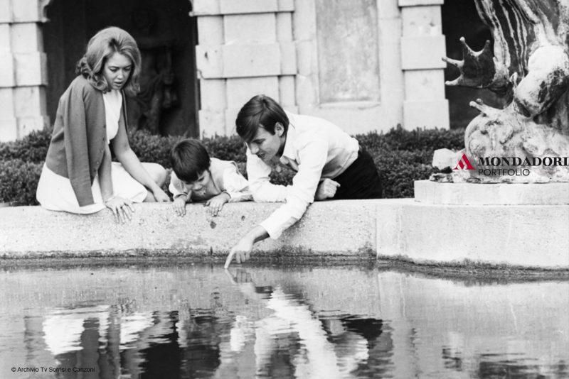 """Faber gioca sul bordo di una fontana a Genova con il figlio Cristiano e la prima moglie Enrica Rignon detta """"Puny""""."""