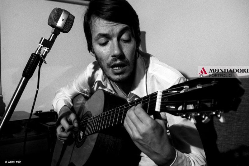 Faber canta e suona la chitarra.